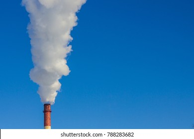 Against the background of a cloudless blue sky, a column of white, thick smoke. Harmful emissions into the atmosphere, pollution of the environment. A bright sunny day.
