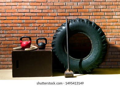 against the background of an orange brick, there are objects for doing, a black tire, a hammer, a rope and weights