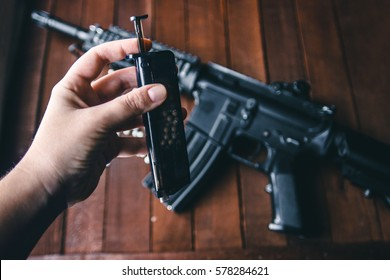 against the background of a person hand holding a rifle loader for filling balloons airsoft