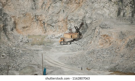 against a background of rubble, Mining industry. Heavy equipment. belaz movement. to transport rocks. miner's day