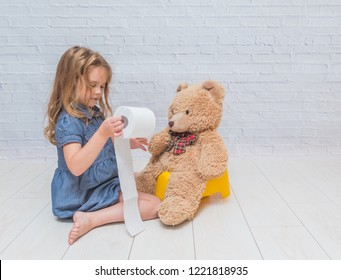a against the background of a white brick wall, the girl sits on a potty with the child, wiping her ass with toilet paper