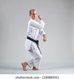 Against a gray background, an active sportsman does formal karate exercises