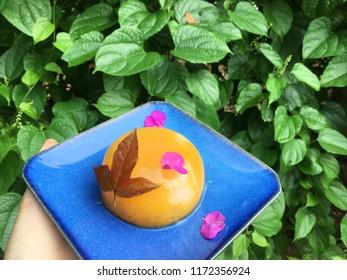 Agar agar ball decorated with maple leaf and flower petals on blue plate. Passion fruit and fresh rambutan agar agar.
