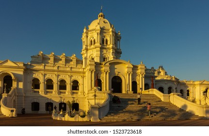 Agartala, Tripura/India - December 5 2017: The setting sun paints the Ujjayanta Palace yellow in the city of Agartala as visitors take pictures of themselves on its stairs.