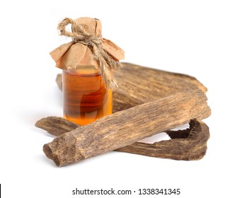 Agarwood, also called aloeswood oudh. With essential oil in pharmaceutical bottle. Isolated on white background.