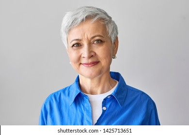 Age and beauty concept. Charming positive mature European female with short gray hair and wrinkles posing isolated, looking at camera with confident smile, wearing stylish blue shirt. Studio image