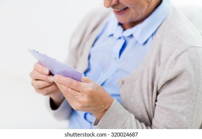 age, game, gamble, poker and people concept - close up of happy smiling senior woman playing cards at home