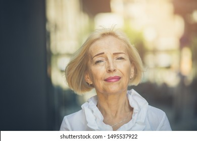 Age give me the gift of confidence. Senior business woman standing on the street.