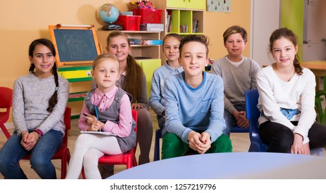 age group of pupil with teacher sitting at table and studying
