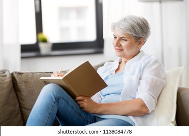age, leisure and people concept - happy senior woman writing to notebook or diary at home
