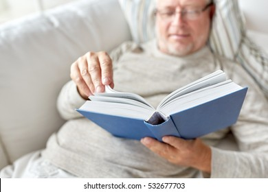 age, leisure and people concept - senior man lying on sofa and reading book at home