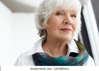 Age, maturity, beauty, style and fashion concept. Close up image of classy stylish senior mature woman with wrinkles, gray hair and natural make up spending leisure time indoors, smiling at camera