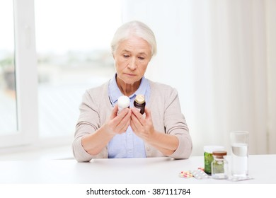 age, medicine, health care and people concept - senior woman looking at jars with medicine at home or hospital office