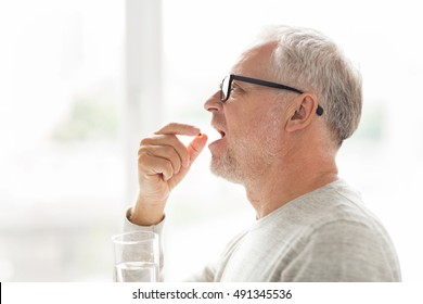 age, medicine, health care and people concept - senior man taking medicine pill at home