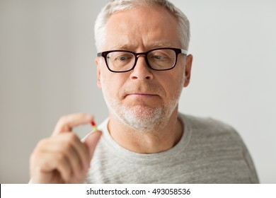 age, medicine, health care and people concept - close up of senior man taking medicine pill at home