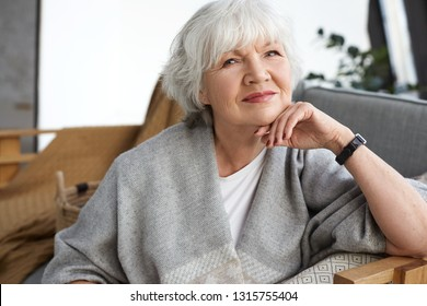 Age, retirement and relaxation concept. Happy cheerful mature retired woman looking at camera with beaming smile, enjoying nice winter day, sitting on couch, wrapped in wide scarf, dreaming