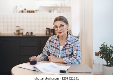 Age, technology, modern lifestyle and occupation concept. Confident female pensioner working remotely from home, sitting in kitchen with laptop computer, notes and cup of coffee, wearing glasses