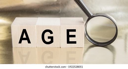 AGE - word from wooden blocks with letters, magnifier, aging concept and retirement planning.