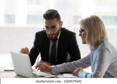 Aged 50s mentor female explain corporate app to middle eastern ethnicity employee use laptop during group meeting in modern office, business people seated at desk negotiating working on common project