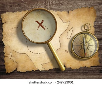 aged antique nautical compass and magnifying glass on table with treasure map