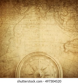 Aged antique nautical compass and old map. Pirate and nautical theme grunge background.