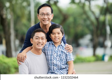 Aged Asian male smiling and looking at camera while standing on blurred background of park and holding hands of shoulders of cheerful son and grandson