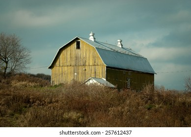 Aged Barn Along the NY State Country Side is a landscape photograph of a yellowish barn found on the country roads of New York State against a stormy bluish gray sky.