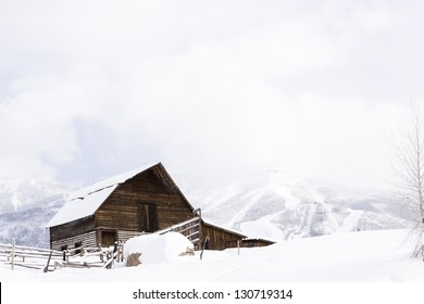 Aged barn on snowy hillside with ski lifts and ski slopes in background.