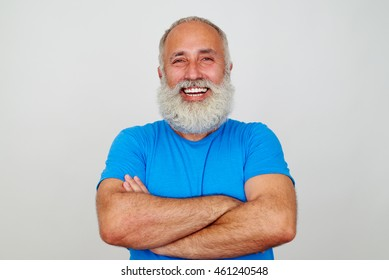 Aged bearded fit man is standing with crossed hands and broad smile isolated against white background