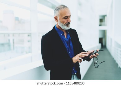 Aged bearded man wearing smart casual clothes typing messages on his mobile phone while standing in the light corridor in the building. CEO reading business emails on his smartphone.
