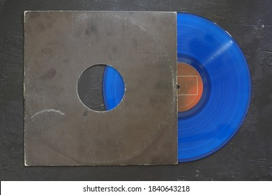 Aged black paper cover and blue vinyl LP record isolated on black background