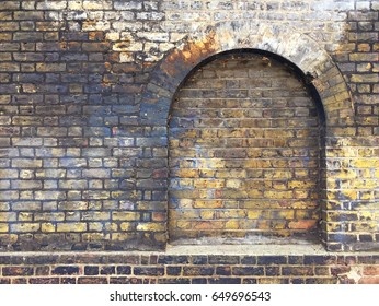 Aged brick wall with arched bricked up window with space for text.