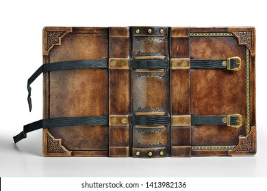 Aged brown leather book cover the gilded frame and with two black belts for keeping the book closed. The book is captured opened while stand up on the table isolated
