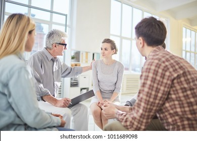 Aged business leader encouraging or lauding one of young employees during psychological session or briefing