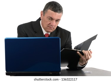 Aged businessman sitting at desk with a laptop isolated on white background