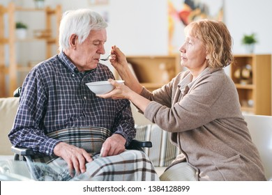 Aged casual woman holding bowl with soup and spoon by her disable husband mouth while helping him to eat dinner