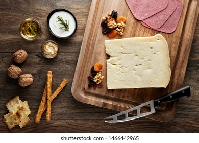Aged cheese on wooden table with wooden cutting board, knife and props. Overhead view.