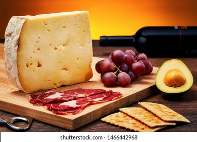Aged cheese on wooden table with wooden cutting board., ham, fruits and crackers