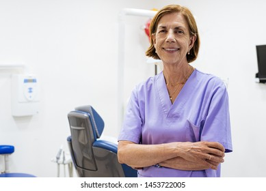 aged confident woman doctor dentist wearing purple lab coat looking at camera