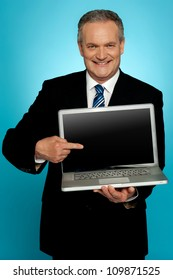 Aged corporate male pointing at laptop screen isolated over gradient background