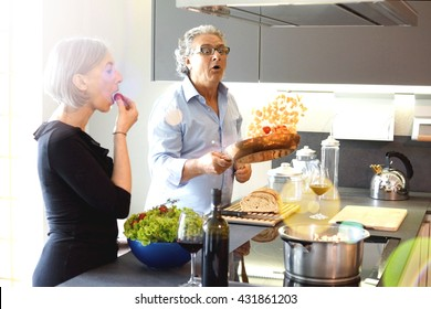 Aged couple cooking and eating in the kitchen