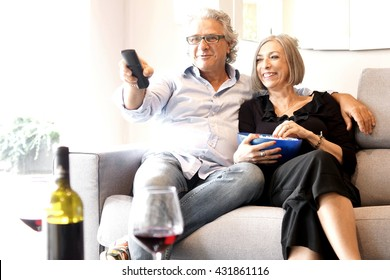 Aged couple eating popcorn and watching tv