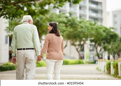 Aged couple holding hands when walking in the park