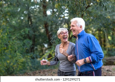 Aged couple jogging in park and smile