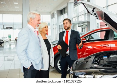 Aged couple look a new car with dealer in the car showroom.
