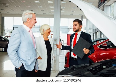 Aged couple look  new car with dealer in car showroom.