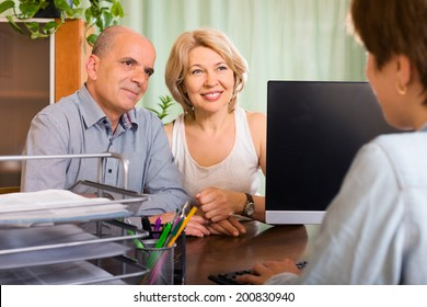aged couple of pensioners talking with employee at office