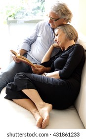 Aged couple reading a book on the couch