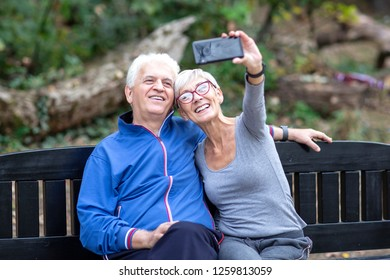 Aged couple sitting at the bench and taking selfie by mobile phone after jogging in the park
