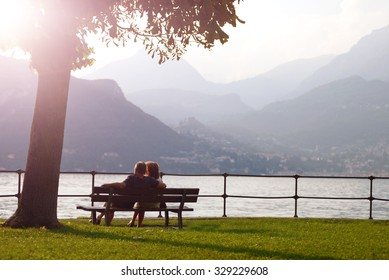aged couple sitting on a bench under a tree and looking at sunset at Como lake, Bellagio, Italy